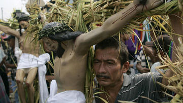 Люди держат статуи Иисуса Христа, во время традиционной процессии во время Страстной недели в Сальвадоре