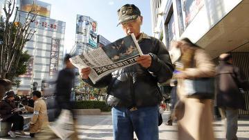 Мужчина читает газету с сообщение о смерти Ким Чен Ира в центре Токио