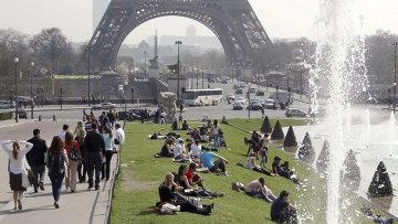 Люди отдыхают на солнце возле Эйфелевой башни в Париже