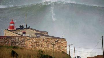 Серфер Гарретт Макнамара покоряет волну в городе Назаре, Португалия