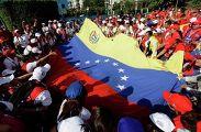 Венесуэльские студенты держат свой национальный флаг