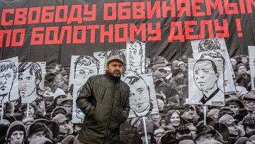 """Журналист и писатель Виктор Шендерович на фоне плаката """"Свободу обвиняемым по Болотному делу"""""""