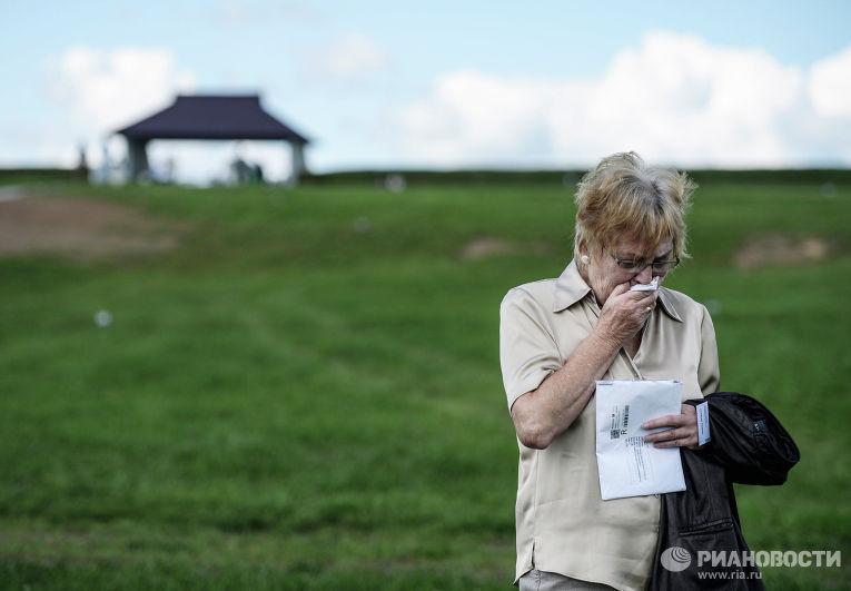 Родственница погибшего воина из Германии плачет на немецком военном кладбище у города Духовщин