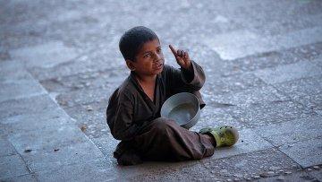 Мальчик просит милостыню на одной из улиц Карачи