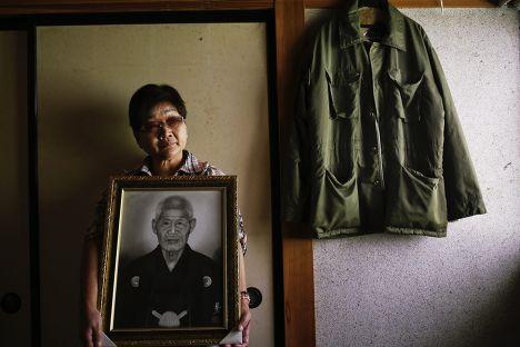 Миеко Окубо с портретом своего тестя, совершившего самоубийство после сообщения об эвакуации, префектура Фукусима