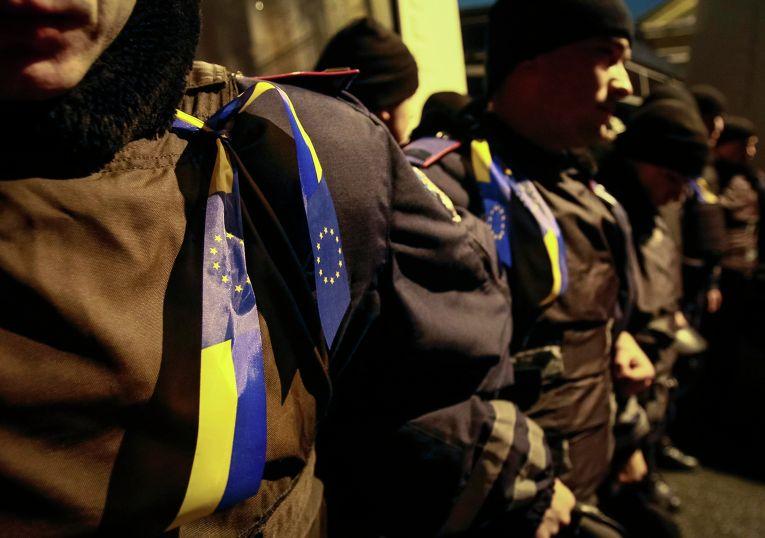 Ленты с украинскими флагами и флагами Евросоюза на полицейских во время митинга в поддержку евроинтеграции, Киев