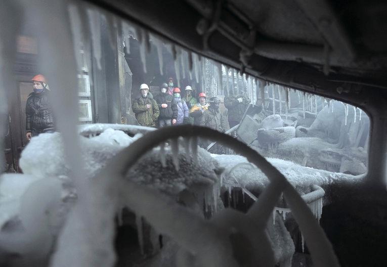 Сгоревшая машина на месте столкновений протестующих с полицией в Киеве