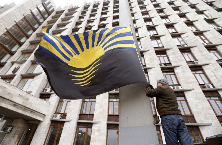Человек вешает флаг Донецка на здание районной администрации