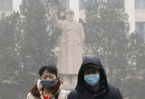 Люди в масках на фоне памятника Мао Цзэдуну в Пекине