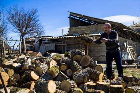 Крымский татарин складывает дрова на участке своего дома в Белогорске