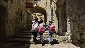 Школьницы идут по улице в Иерусалиме