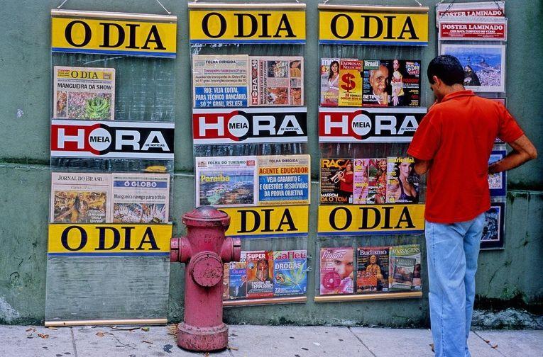 Мужчина смотрит на обложки журналов на улице Рио-де-Жанейро