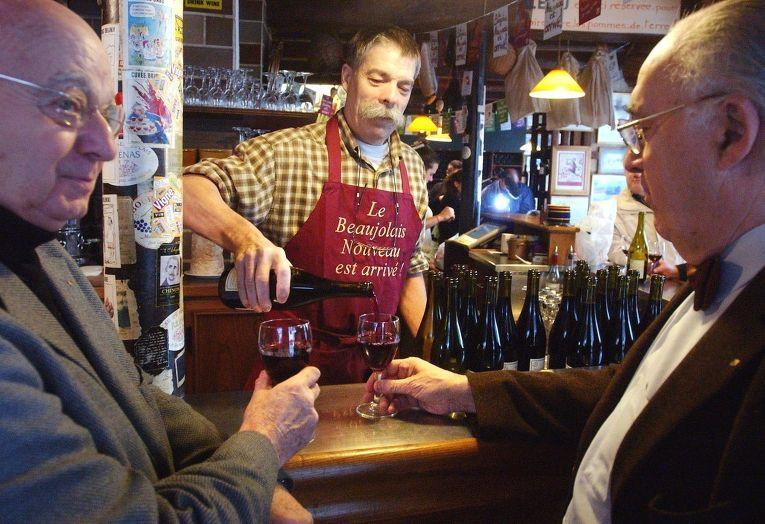 Люди пьют вино в ресторане в Париже