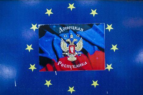 Наклейка с символом Донецкой республики поверх эмблемы Евросоюза в окне магазина в Донецке