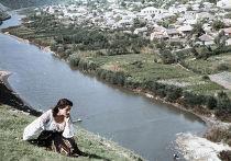 Девушка-молдаванка в национальном костюме сидит на берегу реки Реут