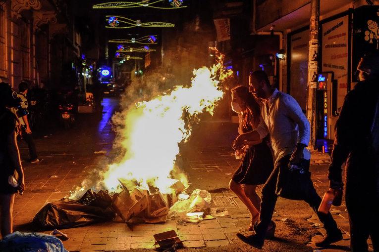Прохожие идут мимо подожжённого мусора на улицах Стамбула