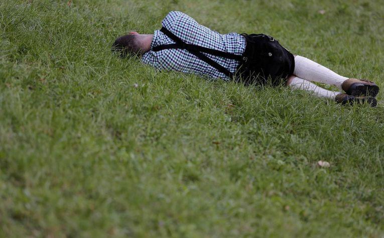 Посетитель пивного фестиваля «Октоберфест» отдыхает на лужайке