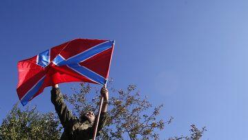 Ополченец устанавливает флаг Новороссии на свой автомобиль