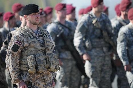 Латвийский и американский солдаты во время церемонии в Риге, посвященной началу совместных учений