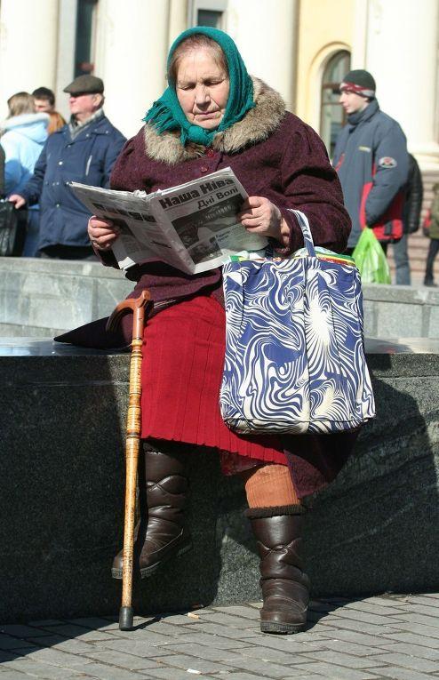 Женщина читает газету на улице Минска