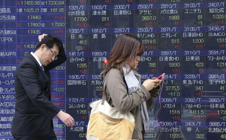 Табло с фондовыми индексами рынка акций в Токио