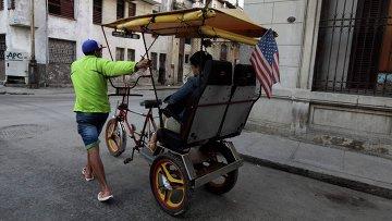 Велорикша с флагом США на улицах в Гаваны