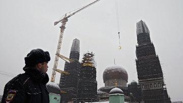Сотрудник полиции наблюдает за установкой полумесяца на минарет Московской Соборной мечети