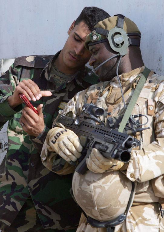 Британский и иракский солдаты смотрят на экран мобильного телефона