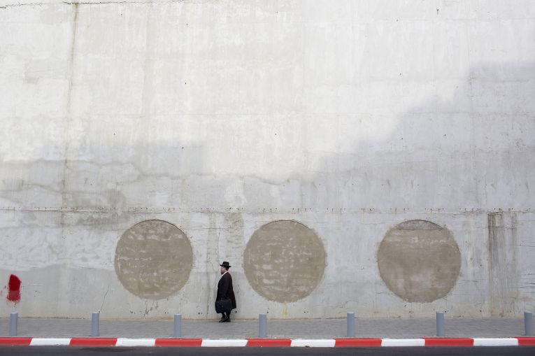 Ультраортодоксальный еврей рядом с недостроенным зданием в городе Рамат-Ган