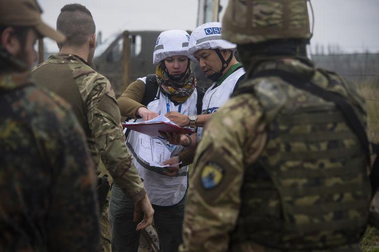 Наблюдатели ОБСЕ разговаривают с украинскими военными рядом с деревней Широкино