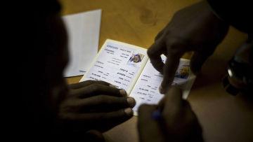 Иммигрант из Эфиопии подписывает документ по прибытии в аэропорт Бен-Гурион в Тель-Авиве