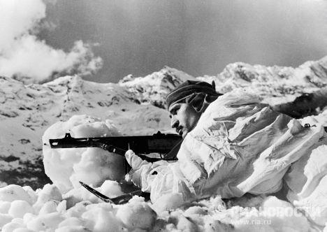 Солдат-грузин с автоматом в маскхалате в горах Кавказа