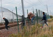 Мигранты перелезают через забор, чтобы пробраться к Евротуннелю