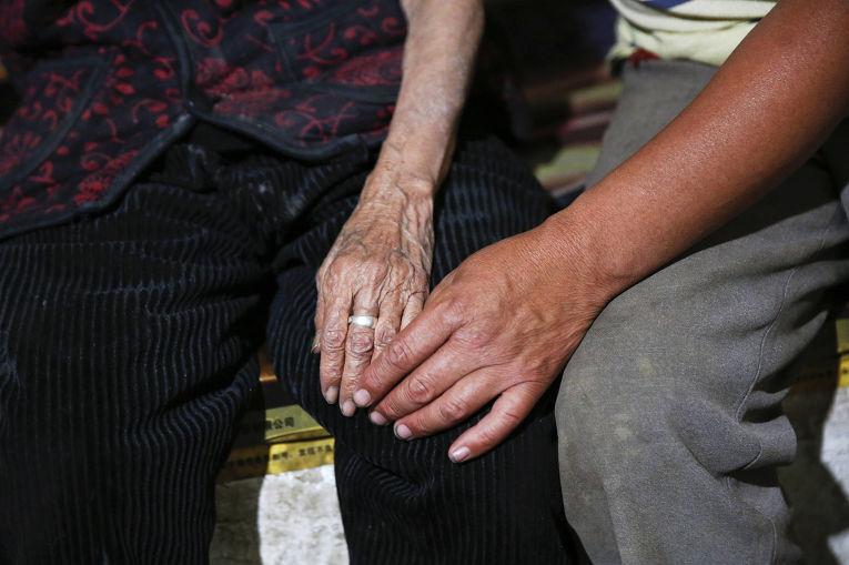 Бывшая «женщина для утешения» Хао Цзюйсян держит за руку сына