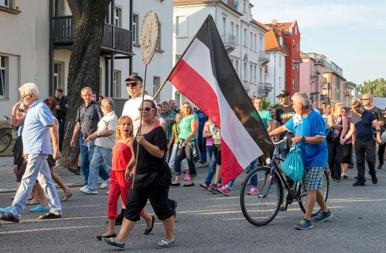Жители Дрездена несут флаг Германской империи во время акции протеста против превращения местного рынка в приют для беженцев