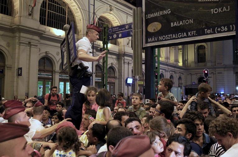 Полицейский пытается контролировать толпу мигрантов на железнодорожном вокзале Будапешта, Венгрия. 31 августа 2015