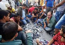 Беженцы заряжают мобильные телефоны в лагере Каратепе на острове Лесбос