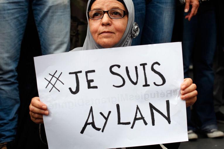 Женщина с плакатом Je suis Aylan на митинге в поддержку беженцев в Париже