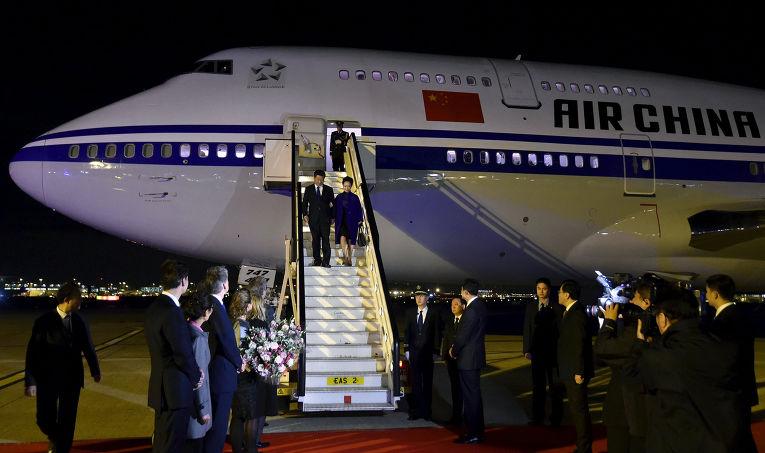 Председатель КНР Си Цзиньпин и его жена Пэн Лиюань спускаются по трапу самолета после прибытия в аэропорт Хитроу