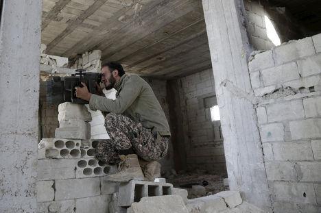 Боец Свободной сирийской армии мониторит позиции сил, поддерживающих Башара Асада, в провинции Хама на севере Сирии
