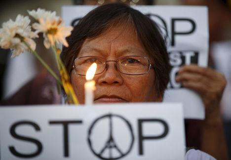 Женщина на акции, посвященной памяти погибших в парижских терактах, в Маниле