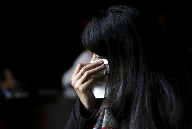Женщина на акции, посвященной памяти погибших в парижских терактах, у французского посольства в Пекине