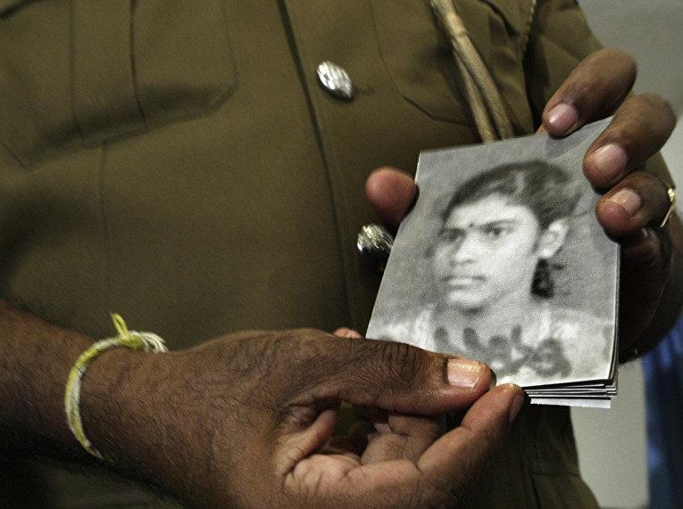 Полицейский показывает фотографии предполагаемой террористки-смертницы, взорвавшей себя у здания министерства в Коломбо