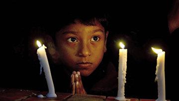 Мальчик во время службы, посвященной погибшим в парижских терактах, в христианской церкви в Исламабаде
