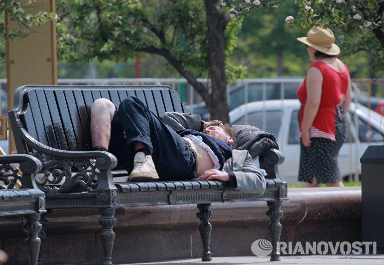 Бездомный спит на скамейке на Театральной площади