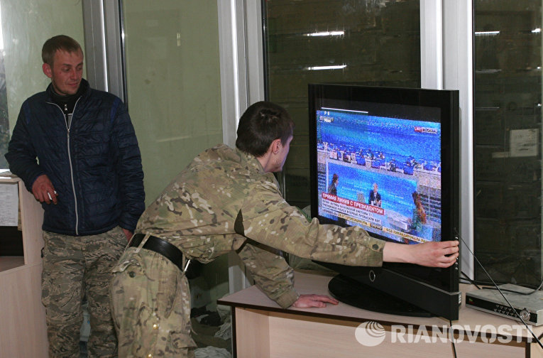 Ополченцы ДНР настраивают телевизор для просмотра ежегодной специальной программы «Прямая линия с Владимиром Путиным»