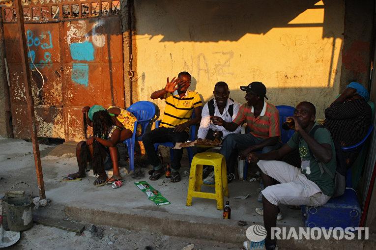 Местные жители отдыхают на одной из улиц города Луанда