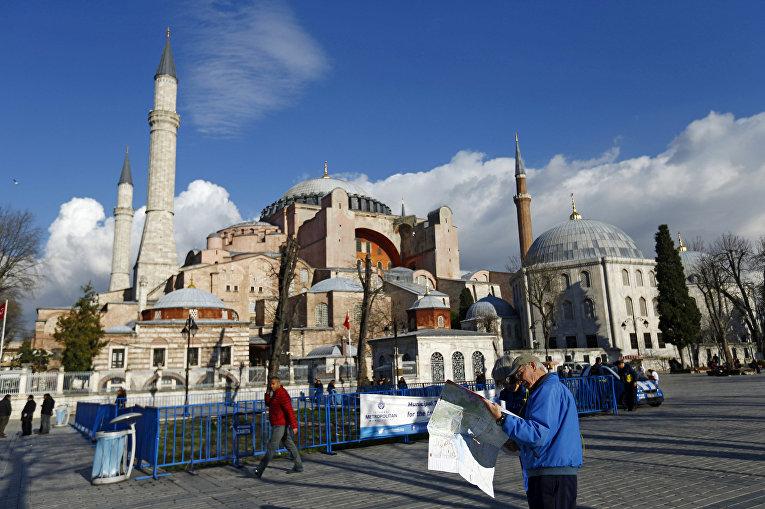 Турист сверяется с картой рядом с собором Святой Софии в центре Стамбула