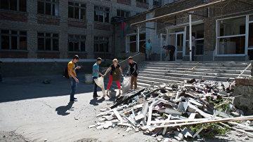 Жители Горловки убирают территорию школы № 16, пострадавшей от ночного обстрела