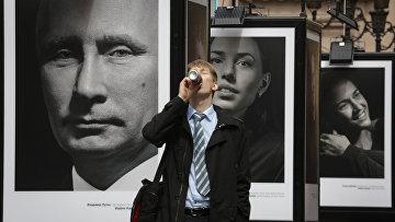 Мужчина пьет напиток на фоне фотографий Владимира Путина и российских спортсменов